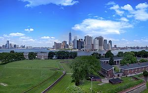 Aerial view of Governors Island in New York City on a sunny day. There is a lawn and some houses in the foreground, and skyscrapers in the background.