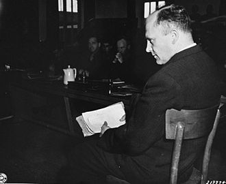 Priest Barracks of Dachau Concentration Camp - Friedrich Hoffman, a Czech priest, testifies at the trial of former camp personnel and prisoners from Dachau. In his hand he holds a packet of records that show that 324 priests died at the camp after being exposed to malaria during Nazi medical experiments.