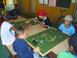 fca7ea203f Crianças jogam futebol de botão.