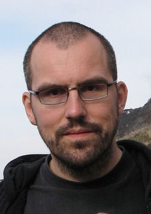 Head shot of a young man with glasses, dark brown buzz cut and stubble.