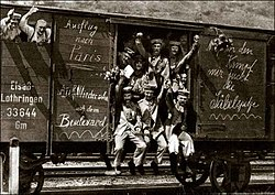 Men waving from the door and window of a rail goods van