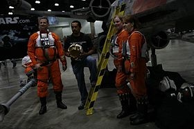 Des cosplayers regroupés devant une reproduction de X-wing T-65.