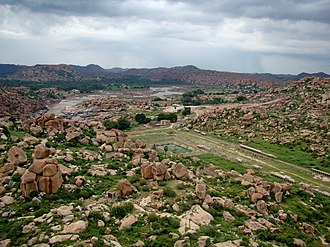 Hampi - Hampi is set in a rocky terrain. Above: one of the many Vijayanagara market ruins, with Tungabhadra River in the background