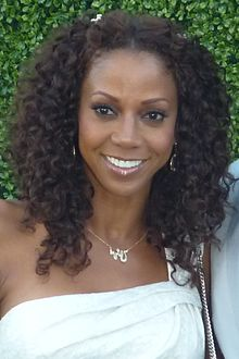 A woman with shoulder-length brown hair, wearing a white dress and a necklace