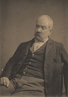 portrait photograph of seated artist with mustache and gray hair