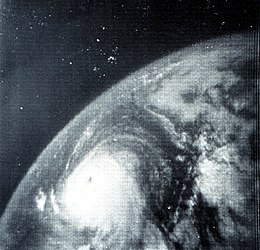 Monochrome satellite image of a tropical cyclone. The tropical cyclone, located at bottom-center, is round and has a distinct eye. Due to the angle of the camera, the curvature of the Earth is clearly visible.