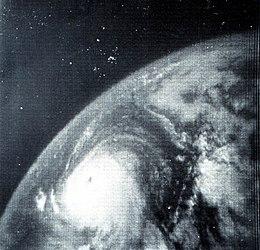 Immagine satellitare monocromatica di un ciclone tropicale.  Il ciclone tropicale, situato in basso al centro, è rotondo e ha un occhio distinto.  A causa dell'angolazione della telecamera, la curvatura della Terra è chiaramente visibile.