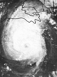 Black and white image of a slightly elongated tropical cyclone with a faintly visible eye at its center. Clouds appear white, while landmasses and bodies of water appear in darker shades of gray.