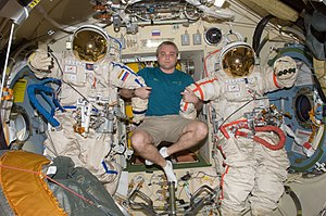 Orlan space suit - Cosmonaut Maksim Surayev next to two Orlan-MK models on the International Space Station