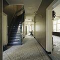 Interieur, overzicht van de gang op de begane grond met tegelvloer en zicht op de trap naar de eerste verdieping, richting achterzijde - Beek en Donk - 20388389 - RCE.jpg