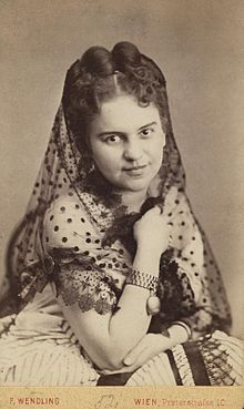 Photograph of a young woman with pinned up hair wearing a white dress and a partially transparent scarf