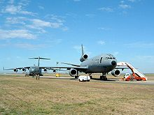 Dois grandes aviões a jato cinza em rampa espaçosa cercada por grama, ambos afastados da pista.  O que está mais perto da câmera tem três motores, enquanto o que está mais ao fundo tem quatro motores.