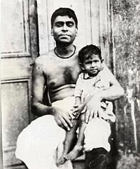 A middle-aged Indian man with bare chest sitting with a child on his lap