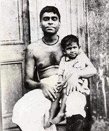 An Indian man with bare chest holding a smiling child on his lap