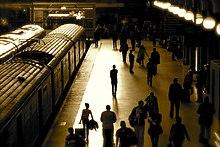 Un quai de gare vue en légère plongée, avec deux trains côte à côte à l'arrêt. La lumière du soir est vive et rasante et une silhouette en contre-jour se distingue au bord du quai, parmi la foule des passagers