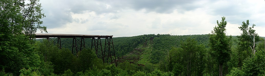 View of the remains of a bridge across a valley. Part of the bridge in foreground and a portion at its far end remain standing, whereas the rest is collapsed and lying on the valley floor.
