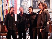 Five men singing around a microphone.