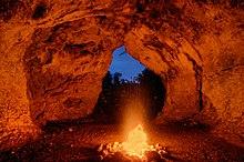 Photographie en couleurs d'un feu consumant des bûches en bois, sa lumière rougeoyante se réfléchissant sur les parois d'une grotte.
