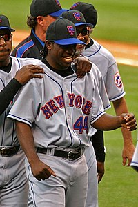 "A man in a grey baseball uniform with ""New York"" and ""44"" on the chest smiles, surrounded by several men in similar uniforms."