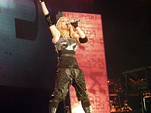 A blond woman singing onstage into a microphone held in her left hand. Her right hand is pointed upwards. The woman is wearing a breast plate and gloves, with knee high boots and ankle covers. Behind her, a rectangular screen displays different symbols.