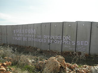 """Ni'lin -  A quote of Martin Luther King """"freedom is never given by the oppressor; it must be demanded by the oppressed"""" written on the separation wall in Ni'lin by International Solidarity Movement activist, February 2012"""