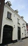 foto van Huis met lijstgevel met banden en hoekblokken van mergel; sterk gewijzigd.