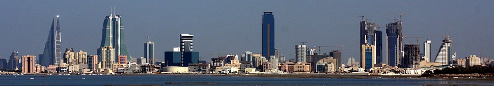 A panoramic view of the skyline of Manama from left to right:1. The twin towers of the Bahrain WTC. 2. The twin towers of the Bahrain Financial Harbor (BFH). 3. The NBB tower (short building next to BFH). 4. The Almoayyed Tower (tallest in the photo, center of image). 5. The Abraj Al Lulu residential project (three towers) under-construction on the far-right).