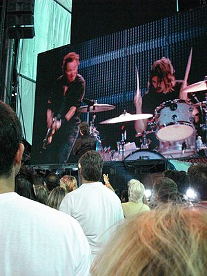 "Jay Weinberg - Max Weinberg (standing in front of stage, in black shirt) watches son Jay on the video screen, during ""Born to Run"" at Giants Stadium in 2008"