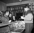 Mensen tijdens het drinken van een glaasje aan de bar terwijl de barkeeper insch, Bestanddeelnr 252-9494.jpg