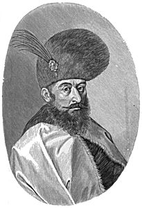 Bearded man with mustache, wearing large round hat with feather