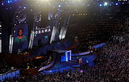 Michelle Obama speaks at a convention; her image and name are projected on a huge screen behind her. The large audience waves vertical blue signs.
