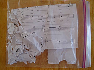A ziplock plastic bag on a wooden surface containing shreds of paper with musical notes and a staff on them
