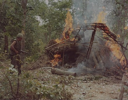 "Men of ""B"" Company, 1st Battalion, 5th (Mechanized) Infantry, 25th Infantry Division set fire to a Viet Cong supply hut during a search and destroy mission in the Michelin Rubber Plantation near Cu Chi Base Camp, 8 April 1966"