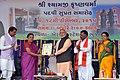Narendra Modi handing over the certificate to the Chief Minister of Gujarat, Smt. Anandiben Patel, marking Shyamji Krishna Varma's posthumous reinstatement to bar, at a function, at Bhuj, in Gujarat on December 18, 2015.jpg