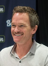 A man with dark blonde hair and mustache smiles away from the camera
