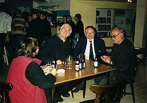 Jan Bucquoy - Jan Bucquoy sitting on the right (dressed in black with glasses, on the corner of the table) during a talk with his producer and with Noël Godin in 2003