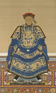 Full-face painted portrait of a severe-looking sitting man wearing a black-and-red round cap adorned with a peacock feather and dressed in dark blue robes decorated with four-clawed golden dragons.
