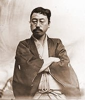 Portrait of an Asian man with moustache dressed in traditional Japanese clothes. He is looking down with his arms crossed.