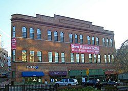 "A large three-story brick building with storefronts on the bottom, rounded-arch windows on the second and third levels and a parapet on top. Hanging from the front is a banner with ""New rental lofts"" and a phone number."