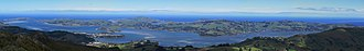 Otago Peninsula - Panorama of Otago Peninsula from Mt. Cargill, looking southeast across Otago Harbour. On the extreme left are the harbour mouth, Aramoana and Taiaroa Head. Near the centre is Harbour Cone, and below it Broad Bay. Portobello and Macandrew Bay are to the left and right respectively. Quarantine Island/Kamau Taurua is mid left above Port Chalmers.
