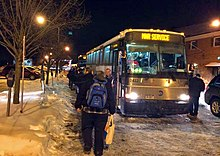 "A line of people, seen from behind, boarding two buses. The nearer one has ""MNR service"" on its front display. It is dark, with orangish-colored streetlights illuminating snow"