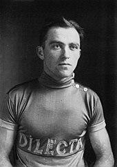 Portrait en noir et blanc d'un cycliste avec un maillot portant l'inscription Dilecta.