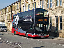 A double-decker bus, painted shiny black with two stripes on the lower part, grey above red. Both stripes sweep up towards the rear crossing a white circular logo of a witch on a broomstick. The bus is standing in front of a row of stone-built, three-storey terraced buildings.