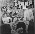 Personnel of USS LEXINGTON celebrate Christmas with make-shift decorations and a firefighting, helmeted Santa Claus. - NARA - 520912.tif