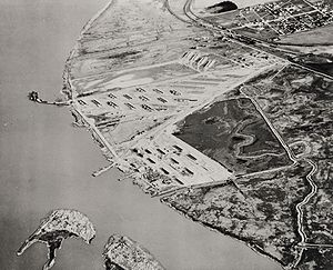 Port Chicago disaster - Aerial photograph looking eastward in early 1944. The town of Port Chicago is in the upper right. The lower left shows utility and personnel piers extending toward the two sections of Seal Island. The munitions loading pier curves to the left beyond 20-odd revetments. Marshy tidal zones separate the munitions pier from barracks buildings near the personnel pier and near the town.