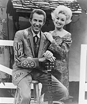 A man in an elaborately-patterned suit, sitting on a stool and leaning on the neck of a guitar. A blonde woman stands to his left, resting her hands on his shoulder.