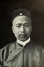 A Chinese man with a shaved head and mustache wearing formal attire.