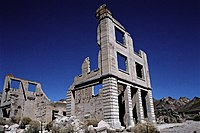 Ruins of a three-story masonry building rise into a cloudless, dark blue sky. The building is roofless, and large sections of it walls are missing. Masonry rubble lies about the building, which has openings for doors and windows but no glass or wood. Another ruin is nearby, and barren hills are visible in the distance.