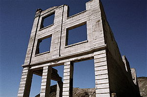 Ruins of a three-story masonry building rise into a dark, cloudless blue sky. The building lacks a roof, and its windows have no glass.