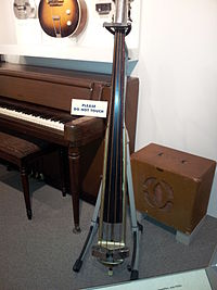 A museum exhibit of vintage musical instruments shows a 1930s amplifier and speaker cabinet and an upright bass with a pickup.